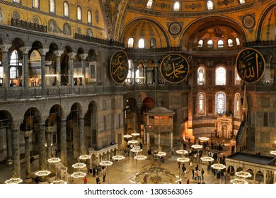 ISTANBUL, TURKEY — MAY 12, 2011. Visitors view the expansive interior of Hagia Sophia, with its crystal chandeliers, calligraphied medallions, and high domed ceiling decorated with painted designs.