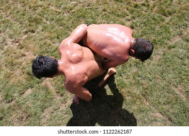 ISTANBUL, TURKEY - MAY 12, 2018: Oil wrestlers compete during Etnospor Culture Festival. Oil wrestling also called grease wrestling is the Turkish traditional sport.