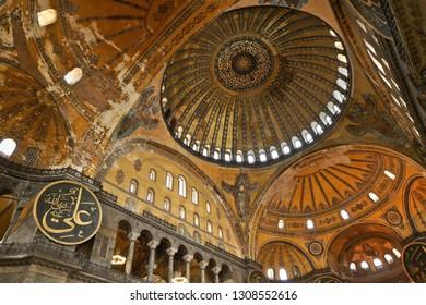 ISTANBUL, TURKEY — MAY 13, 2011. The expansive interior of Hagia Sophia Museum features calligraphied medallions of the caliphs, side galleries, and a high vaulted ceiling with painted designs.