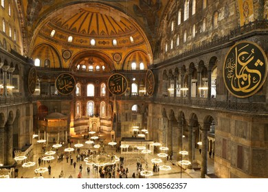 ISTANBUL, TURKEY — MAY 13, 2011. Visitors view the expansive interior of Hagia Sophia, with its crystal chandeliers, calligraphied medallions, and high domed ceiling decorated with painted designs.