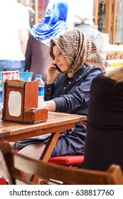 ISTANBUL, TURKEY - MAY 14, 2014 - Young Turkish woman with a scarf uses her cell phone outside a restaurant in Emininou area in Istanbul, Turkey