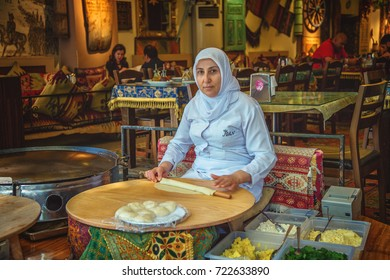 ISTANBUL, TURKEY - MAY 2, 2017: Turkish woman rolls the dough for preparing traditional Turkish pastries - gozleme on a stove. At restaurant