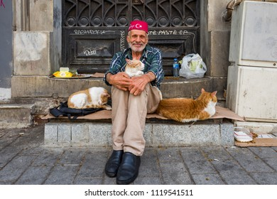 Istanbul, Turkey - May 20, 2018: Old man with streets cat smiles at camera in Taksim district.
