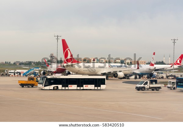 ISTANBUL, TURKEY - MAY 23, 2016: White airplane is being serviced by the ground crew. Bus with passengers.