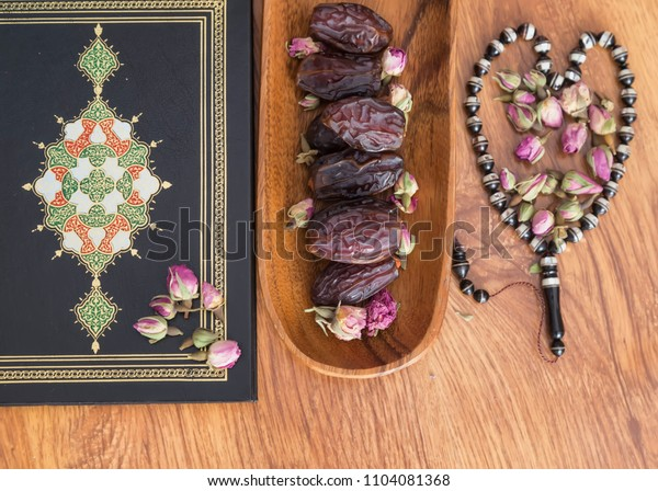 Istanbul , Turkey - May 23, 2018 ; Koran, date and rosary on the wooden background with rose for Islamic concept. Holy book Quran for Muslims for eleven month sultan Ramadan.