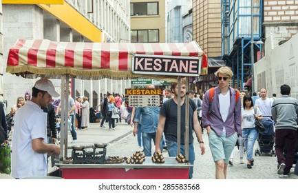 ISTANBUL, TURKEY - MAY 30, 2015: Chestnut seller and tourists. Eminonu, Istanbul, Turkey