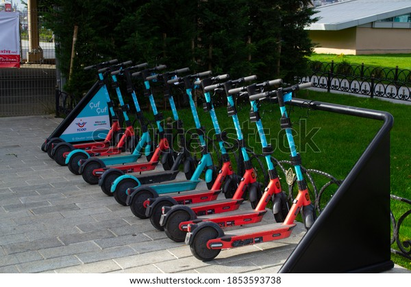 Istanbul / Turkey - November 12, 2020: Electric Scooter rent station. Scooters in a row in the park. Ecology friendly transportation