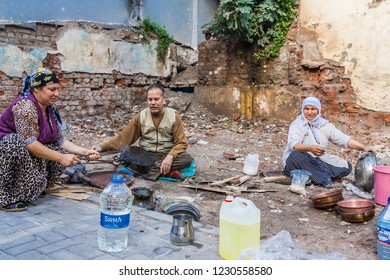 Istanbul, Turkey, November 13, 2012: Tinkers tinning pots in the street in the Balat District.