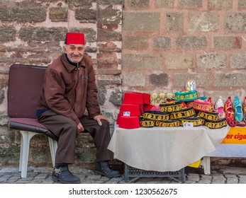 Istanbul, Turkey, November 13, 2012: Elderly Turkish man selling Turkish hats outside the Chora Museum in Balat.