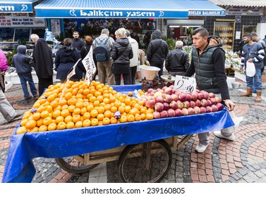 Istanbul, Turkey- November 16, 2014: Young men are pushin wheelbarrows with fruits and vegetables on a market street in Istanbul.