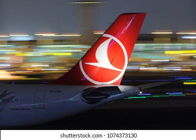 ISTANBUL, TURKEY - NOVEMBER 28, 2017; Turkish Airlines (TK) Airbus A330 passenger widebody jet aircraft tail with airline logo airport in night at Ataturk (IST) airport with light trails in backround