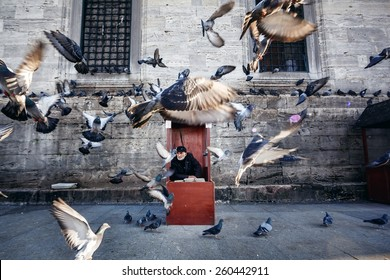 ISTANBUL, TURKEY - NOVEMBER 28: Old photographer in red booth with feed for pigeons flying in front of him, Istanbul, Turkey on November 28, 2014