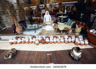ISTANBUL, TURKEY - NOVEMBER 29: Woman sitting in showcase and making pitas for sale, Istanbul, Turkey on November 29, 2014