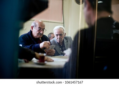 ISTANBUL, TURKEY - NOVEMBER 7, 2009:  Man looks over the shoulder of another playing cards inside a cafe in the Fatih district of Istanbul.