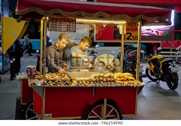 ISTANBUL, TURKEY. October 19, 2017. Two unknown Turkish teenagers making themselves grilled corn cob at a mobile kiosk in central Istanbul.
