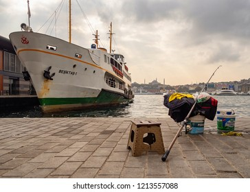 ISTANBUL, TURKEY - OCTOBER 20, 2018: Fishing rod and a public tranportation boat on touristic eminonu karakoy area with view of istanbul old town blue mosque and hagia sophia in the background.
