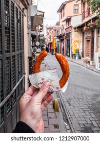 Istanbul, Turkey - October 21, 2018: A man's hand holding tulumba dessert, a traditional Turkish dessert in the old streets of Balat, Istanbul