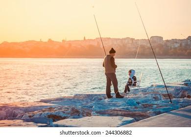 ISTANBUL, TURKEY, October, 26, 2014: Man is fishing with his son on Marmara sea quay in Bakirkoy in Istanbul, Turkey.