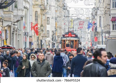 ISTANBUL, TURKEY - OCTOBER 4, 2018: Red nostalgic tram is moving among crowded people on the Istiklal street. Istiklal Street is busy, vibrant and most popular destination in Beyoglu, Taksim, Istanbul