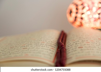 Istanbul/ Turkey - October 6, 2018 ; Koran and rosary beads on the wooden background with lantern or candle for Islamic concept. Holy book quran for Muslims holiday, Ramadan,blessed Friday message.