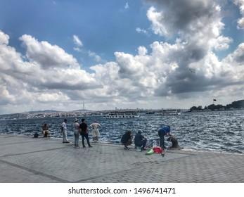 ISTANBUL - TURKEY, September 05, 2019: Local fisherman fishing at the seaside overlooking Karakoy coastline.
