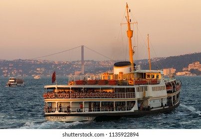 ISTANBUL, TURKEY - SEPTEMBER 11, 2005 : A packed passenger ferry on the Bosphorus Strait at sunset with the 15 July Martyrs Suspension Bridge in the distance.