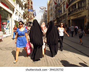 Istanbul, Turkey - September 15, 2012: Women in western apparel stroll past ladies in burkas on Istikal Caddesi, a popular shopping avenue. A suicide bomber struck on this street on March 19, 2016.