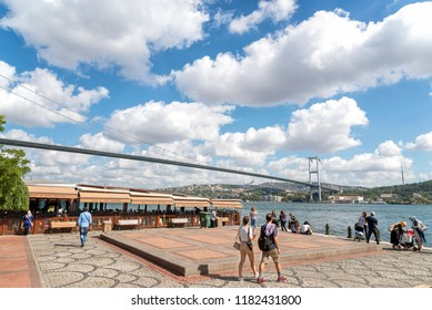 ISTANBUL, TURKEY, SEPTEMBER 17, 2018: People walking at Ortakoy seaside, Bosphorus Bridge (15th july martyrs bridge) at the background, famous landmark of Istanbul, Turkey.