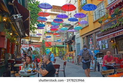 Istanbul, Turkey - September 18th 2020. Colourful umbrellas hang from the sky covering a street of bars and restaurants in the Moda district of Kadikoy on the Asian side of Istanbul,