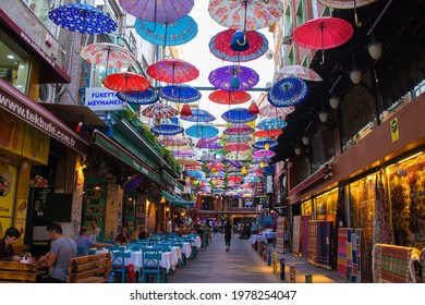 Istanbul, Turkey - September 18th 2020. Colourful umbrellas hang from the sky covering a street of bars, restaurants and shops in the Moda district of Kadikoy on the Asian side of Istanbul,