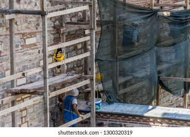 Istanbul, Turkey, September 22nd, 2018: Construction workers on a scaffold during repair and restoration work on a wall of Topkapi Palace