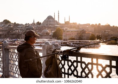 Istanbul, Turkey - September 25, 2014: Local fisherman is fishing near the Bosphorus at Galata Bridge in Istanbul, Turkey. Sunset time. Istanbul's iconic Galata Bridge is a top spot for fishing.
