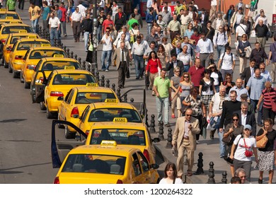 ISTANBUL / TURKEY - SEPTEMBER 28th, 2007: Queuing yellow taxis next to a crowd of people on the sidewalk