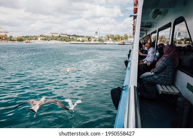 Istanbul, Turkey - September 5, 2020: People wearing masks sail on a public ferry while seagulls are begging for food.