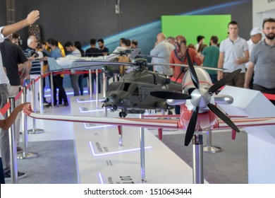 Istanbul, Turkey - September-18,2019: Model of the plane called Hurkus introduced at Teknofest 2019 festival. Helicopter and people in background.