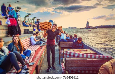 ISTANBUL, TURKEY: Young guy, seller of turkish bagels - simit and visitors of cafe on the waterfront of Uskudar meeting sunset with view of Maiden's tower on October 3, 2017