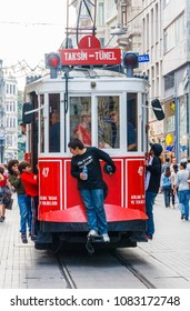 istanbul, Turkey-8th October 2011: Kids hitching a free ride on Retro tram on Istiklal Caddesi. The tram runs to Taksim Square .