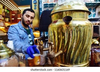 ISTANBUL, TURKEY-APRIL 22, 2018: Merchant man with mustache pressing Sahlep tea tradition beverage from large brass pot into paper container grab cub for sale at bazaar market, local business concept