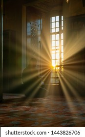ISTANBUL, TURKEy-SEPTEMBER 24, 2016 :  a man reads Koran or Al Quran with intentional lens flare sun setting up inside Sultanahmet mosque in Istanbul, Turkey.