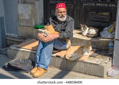 ISTANBUL,TURKEY 07,2016: Old man and cat sitting at Salim street