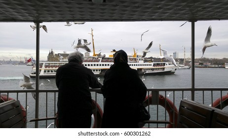 Istanbul,Turkey - 26 February 2017 : Two people feeding Sea Gulls from Board of Ferry at Sunrise