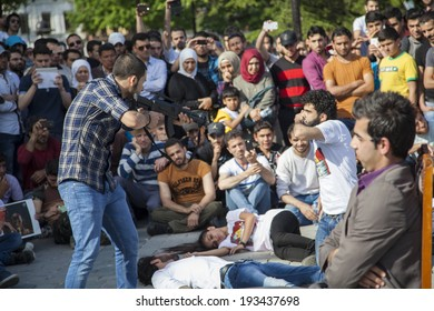 ISTANBUL/TURKEY - MAY 18 2014: Syrian Demonstrators perform short sketch that illustrates Bashar Al-Assad's attachment to the presidency, and how far he will go to keep it.
