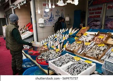 ISTANBUL,TURKEY-FEBRUARY 01,2017:Turkish man selling at a fish market stall in Karakoy, Istanbul.