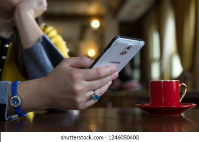 Istanbul/Turkey-November 28, 2018; Close up of women's hands holding Samsung mobile phone with space screen, girl watching video,writing message,shopping online and drink coffee in the cafe concept.