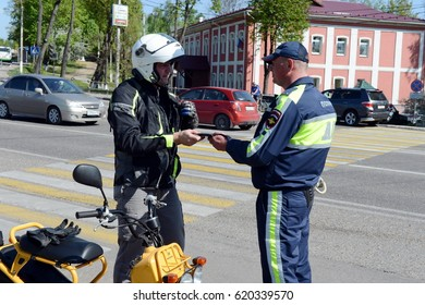 ISTRA, RUSSIA - MAY 14,2016:The inspector of traffic police checks the documents of the motorcycle.