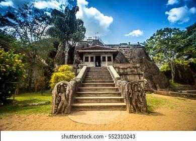Isurumuniya Viharaya (monastery) with its old buildings, white Stupa and lush garden around the granite rock, Anuradhapura, Sri Lanka.