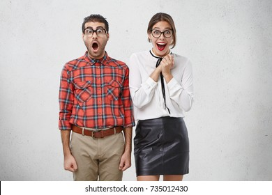 It` s unbelievable! Shocked man looks surprisedly through glasses, keeps mouth opened, hears unexpected news and joyful beautiful female wears red lipstick being glad to be promoted by employee