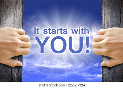"""""""It starts with YOU"""" text floating in the Sky while 2 hands opening a wooden door."""