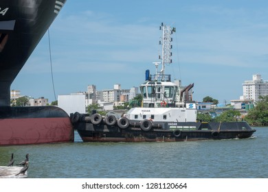 Itajai, Santa Catarina / Brazil - 01 03 2019: Tugboat HADAR operates on the bow of the container ship MSC ARICA