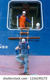 Itajai, Santa Catarina / Brazil - 04 01 2017: a harbour pilot climbs the ladder to board a ship while two crew members watch him